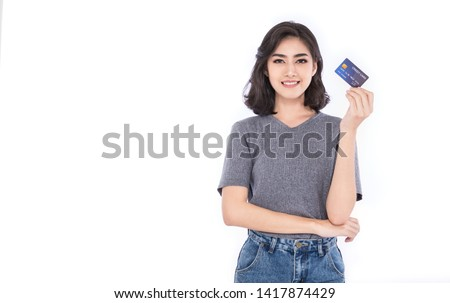 Portrait of young smiling beautiful Asian woman presenting credit card in hand showing trust and confidence making payment, online shopping financial account telemarketing e-commerce concept
