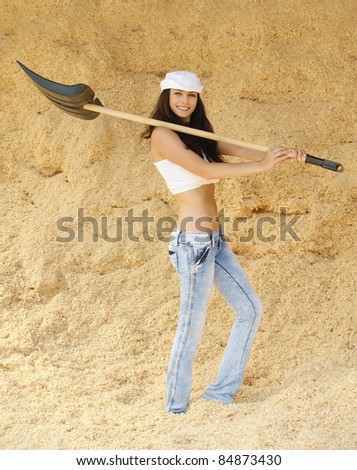 Portrait of young smiling beautiful brunette woman holding spade, standing in sawdust.