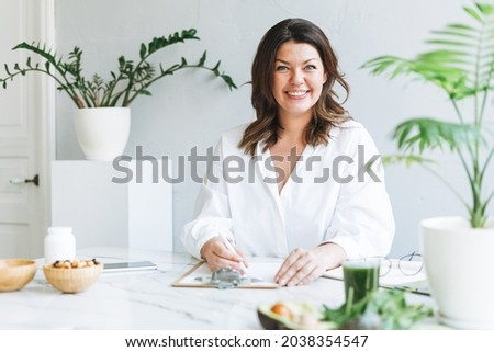 Portrait of Young smiling brunette woman doctor nutritionist plus size in white shirt working at laptop at modern bright office room Foto stock ©