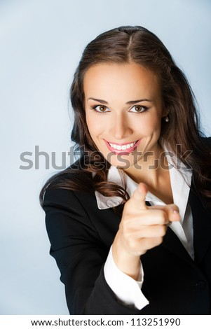 Portrait of young smiling business woman pointing finger at viewer, over blue background
