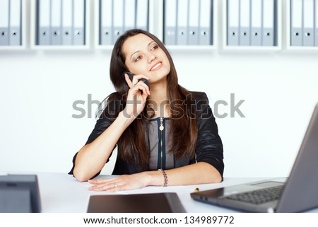 Portrait of young smiling business woman sitting at office desk and talking on cell phone - stock photo