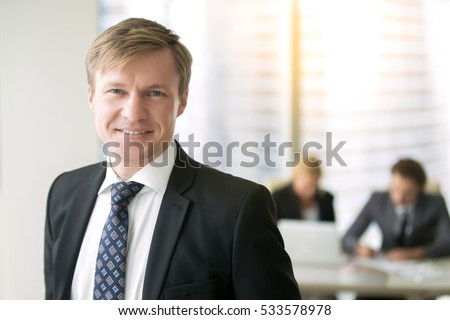 Portrait of young smiling businessman, successful entrepreneur, having triumph at the meeting, built an empire, top manager with a great deal of experience. His subordinates working on the background