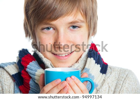 Portrait of young smiling cute frozen teenager in a scarf and with blue cup, isolated on white,