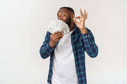 Portrait of young smiling dark skin african american man in white t shirt holding money and showing okay sign isolated on gray background