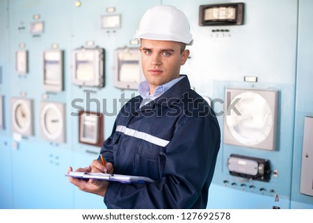 Portrait of young smiling engineer taking notes in control room