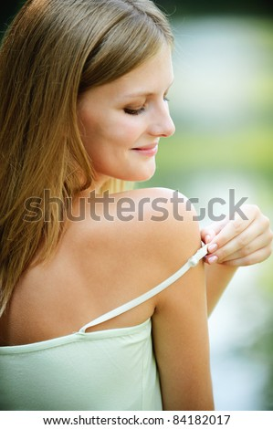 Portrait of young smiling fair-haired woman putting out strap of her dress at summer green park.