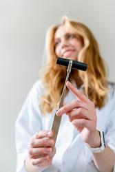 Portrait of Young smiling female doctor. conducts neurological examination with neurological hammer. close-up of neurological hammer. Positive welcome.