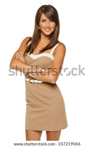 Portrait of young smiling female in beige dress standing with folded hands, over white background
