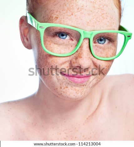 Portrait of young smiling freckled girl wearing glasses