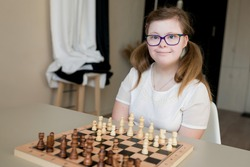 Portrait  of young smiling girl with Down syndrome playing chess on the game board. Disabled kids examining chessboard at home. Development of capacity children with development delays