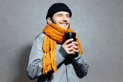 Portrait of young smiling man with coffee thermo mug in hands, with wireless earbuds, wearing orange scarf on background of gray.