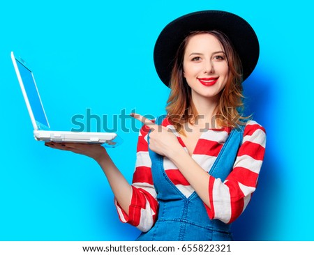 Portrait of young smiling red-haired white european woman in hat and red striped shirt with jeans dress and laptop on blue background