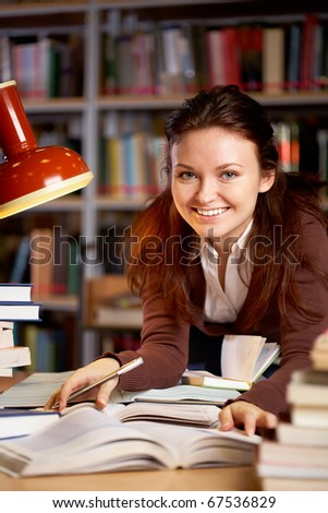Portrait of young smiling teacher looking at camera in college library