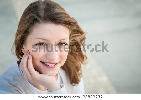 Portrait of young smiling woman - grey background