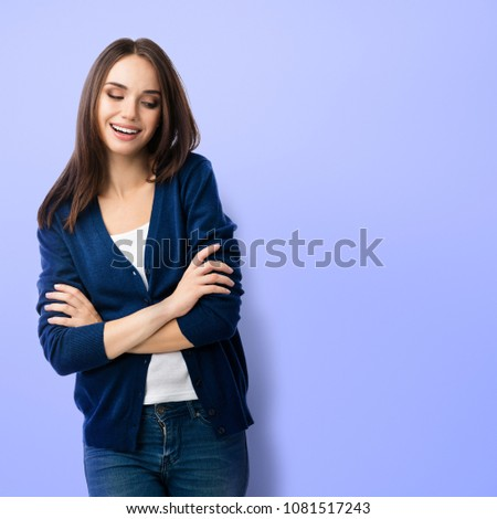 Portrait of young smiling woman in casual smart blue clothing with crossed arms, over violet background, with copyspace for slogan, advertising or text message. #1081517243
