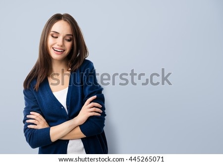 Portrait of young smiling woman in casual smart blue clothing with crossed arms, with copyspace area for text or slogan #445265071