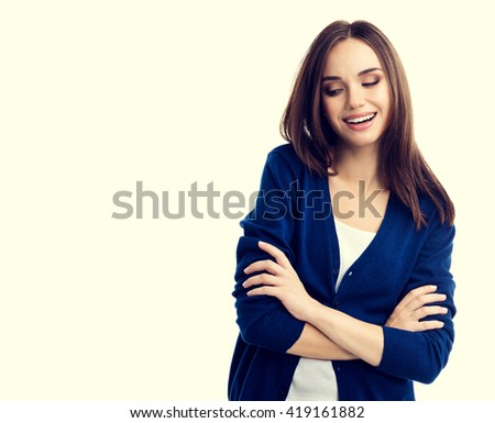 Portrait of young smiling woman in casual smart blue clothing with crossed arms, with copyspace for slogan or text message #419161882