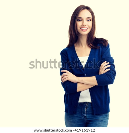 Portrait of young smiling woman in casual smart blue clothing with crossed arms, with copyspace for slogan or text message #419161912