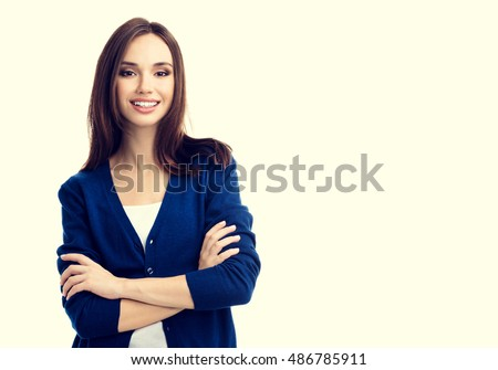 Portrait of young smiling woman in casual smart blue clothing with crossed arms, with copyspace for slogan or text message #486785911
