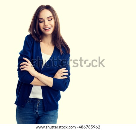 Portrait of young smiling woman in casual smart blue clothing with crossed arms, with copyspace for slogan or text message #486785962