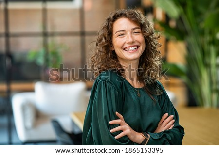 Portrait of young smiling woman looking at camera with crossed arms. Happy girl standing in creative office. Successful businesswoman standing in office with copy space.