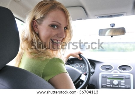 Portrait of young smiling woman siting behind steering wheel inside car