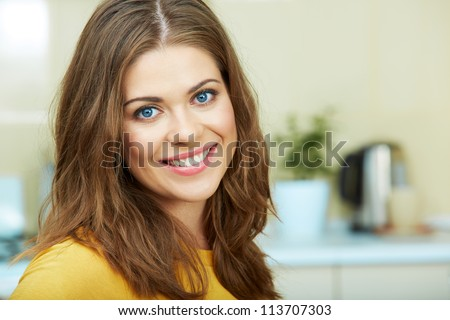 Portrait of young smiling woman sitting against home kitchen background. Close up.