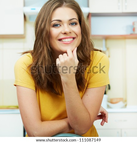 Portrait of young smiling woman sitting against kitchen background. Close up.