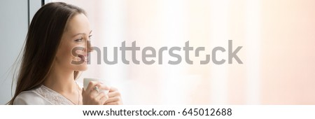 Portrait of young smiling woman standing at window wearing beautiful lingerie, dreaming and relaxing with cup of coffee. Horizontal photo banner for website header design with copy space for text  #645012688