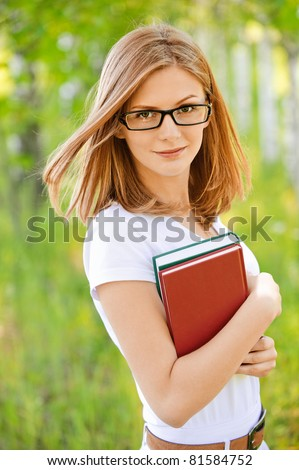 Portrait of young smiling woman-student in glasses and with books in hands on green background of city park.