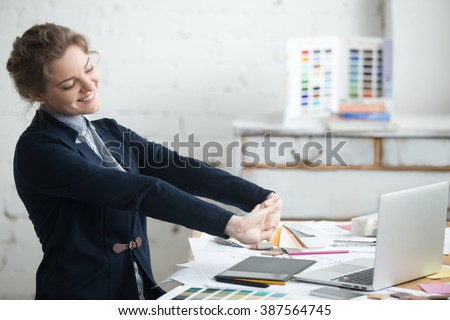 Portrait of young smiling woman wearing suit sitting at home office desk in front of laptop, stretching with enjoyment after the work is done, looking at screen with happy expression