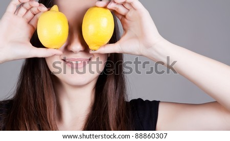 Portrait of young smiling woman with lemons in front of eyes