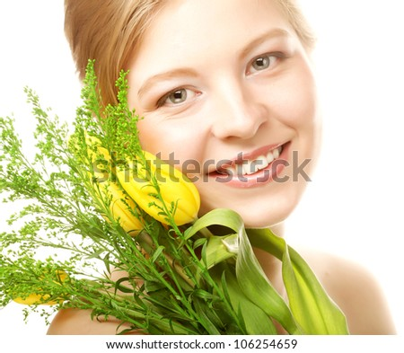 Portrait of young smiling woman with yellow tulips