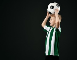 portrait of young soccer player, football school student, kid boy in red white striped uniform holding ball on his head and looking at copy space over black background. Side view
