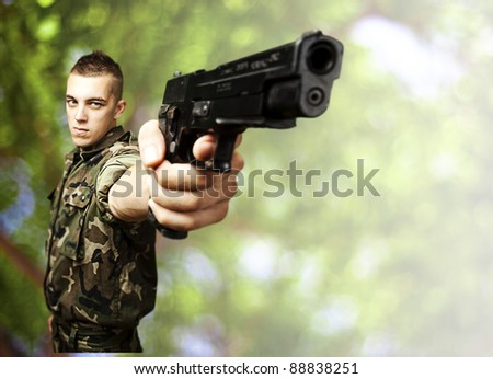 portrait of young soldier aiming with gun against a nature background - stock photo