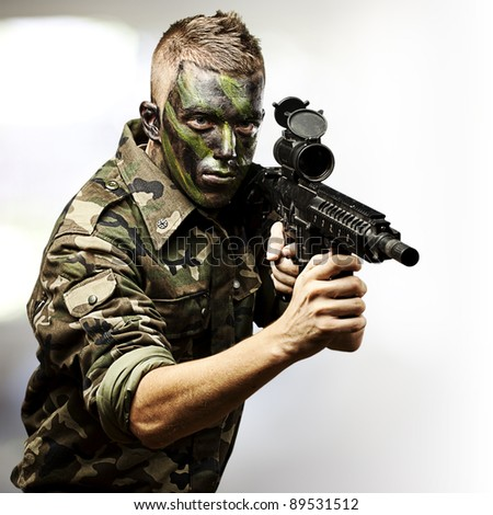 portrait of young soldier aiming with rifle against a abstract lights background - stock photo