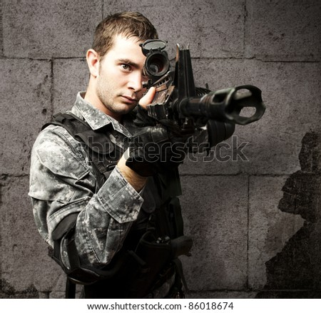 portrait of young soldier aiming with rifle against a grunge background
