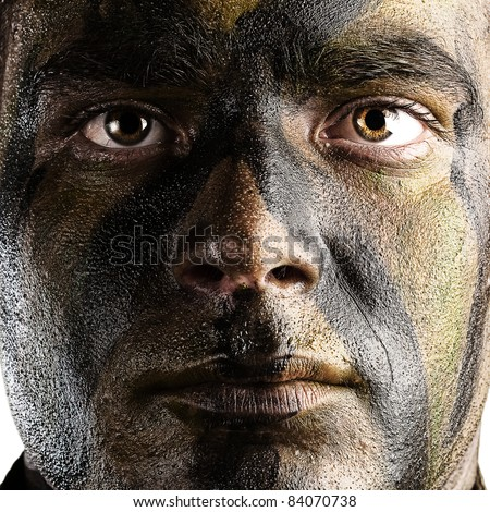 portrait of young soldier face with jungle camouflage paint against a white background