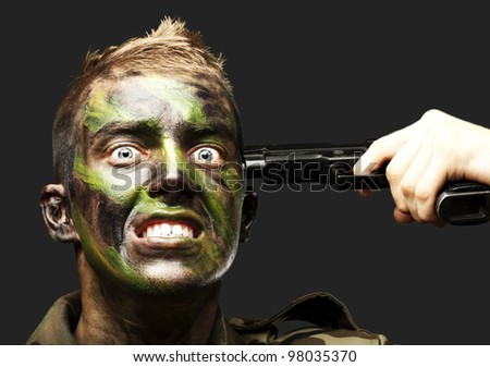 portrait of young soldier gesturing suicide over black background - stock photo