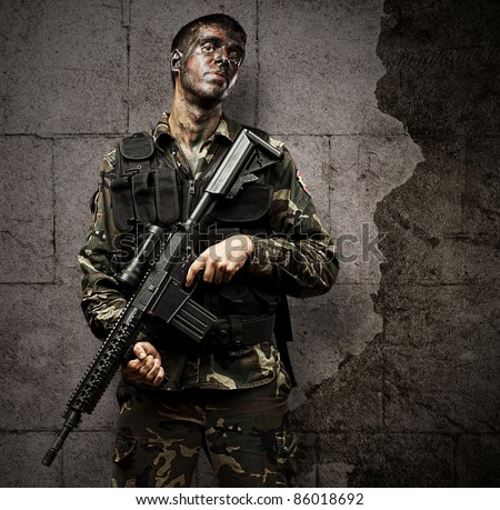 portrait of young soldier holding rifle against a grunge background