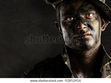 portrait of young soldier painted with jungle camouflage against a grunge wall