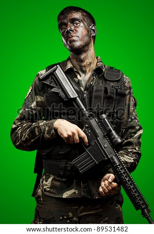 portrait of young soldier painted with jungle camouflage holding riffle over green background