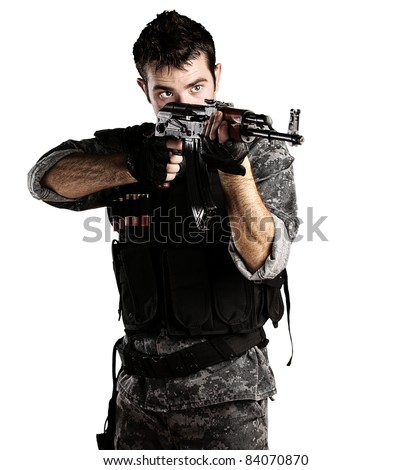 portrait of young soldier pointing with rifle against a white background