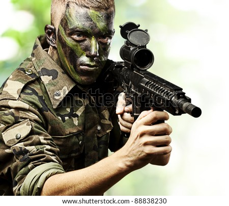 portrait of young soldier pointing with rifle in the jungle