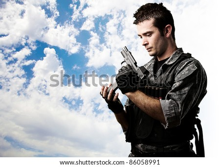 portrait of young soldier reloading the gun against a cloudy sky background