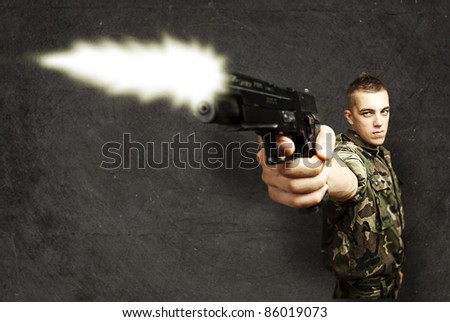 portrait of young soldier shooting with gun against a grunge background