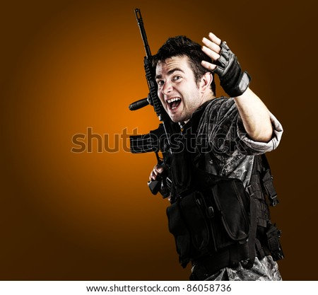portrait of young soldier telling that follow him against golden background