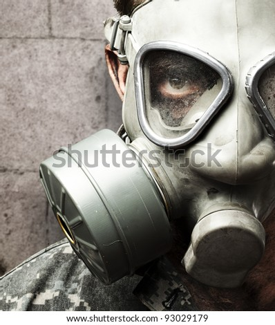 portrait of young soldier wearing gas mask against a grunge bricks wall