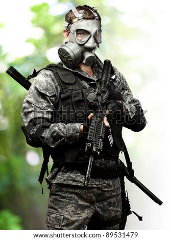 portrait of young soldier with gas mask and rifle against a nature background