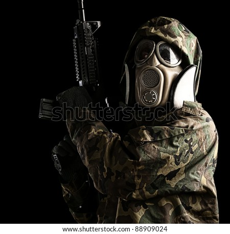 portrait of young soldier with jungle camouflage and gas mask against black background